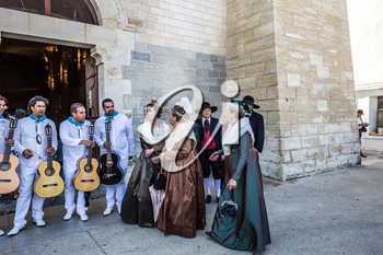 Saint-Marie-de-la-Mer, Provence, France - May 25, 2015. World Festival of Gypsies. Residents of the city in ancient costumes and a musical ensemble with guitars. Medieval cathedral of Notre Dame