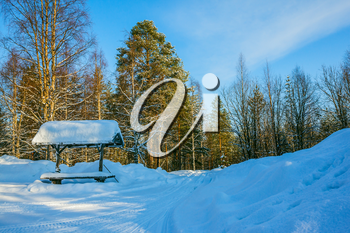Snowy winter in the Arctic. At the bus stop is a large snowdrift. Travel to Lapland. Winter fairy tale in a sunny frosty day. The concept of active and extreme tourism