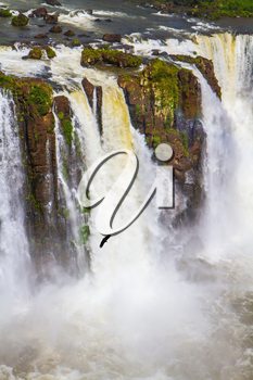 Complex of waterfalls Iguazu on the border of three countries. The most full-flowing waterfalls Iguazu. Andean condors fly in the water dust. Concept of active and extreme tourism