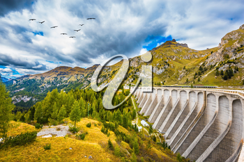 Powerful dam blocked the lake. Mountain Lake Lago di Fedaia, Dolomites. The concept of ecological and extreme tourism