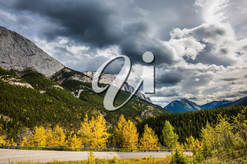 Gorgeous stormy sky in October. Rocky Mountains of Canada.  Road among autumn forest