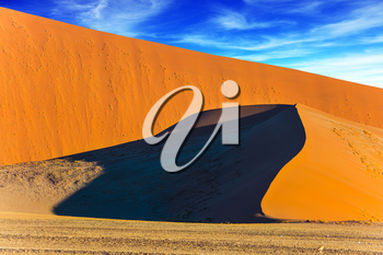 Sharp border of light and shadow over the crest of the dune. Namibia, South Africa. Sunset in the desert. The concept of extreme and exotic tourism
