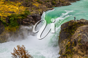Southern Province of Chile. Lonely woman photographer on a cliff near the turquoise waterfall Salto Grande. Concept of active and ecological tourism