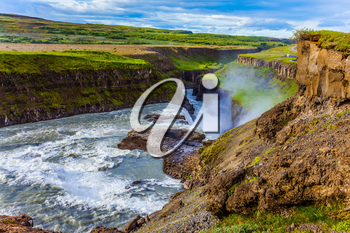 Summer day. Huge masses of water crash into the abyss. The most picturesque waterfall in Iceland - Gullfoss. The concept of extreme and phototourism