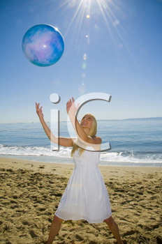 Royalty Free Photo of a Woman Catching a Ball on the Beach