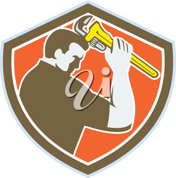 Illustration of a plumber holding monkey wrench viewed from the side set inside crest shield on isolated background done in retro style.