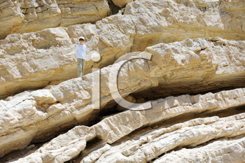 Royalty Free Photo of a Boy on the White Stones of Makhtesh Ramon, a Unique Crater in Israel