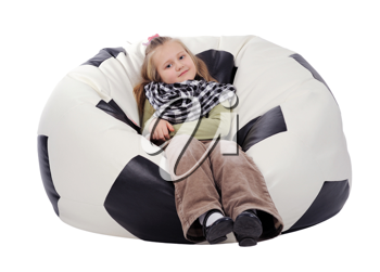Girl with long blonde hair sitting on an inflatable chair in the form of a soccer ball, isolated on a white background