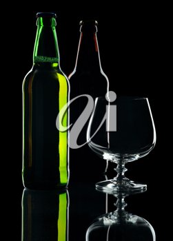 Bottles of lager beer from green and brown glass, isolated on a black background.