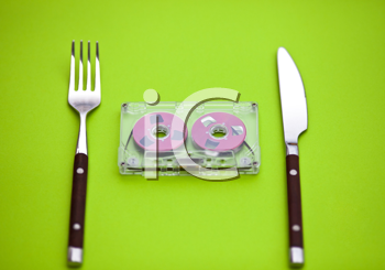 Royalty Free Photo of an Audio Tape Between a Fork and Knife