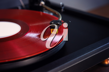 Vintage Stereo Turntable Plays Red Vinyl Record Album, Tonearm with Headshell Closeup