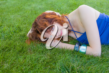 very  pretty red headed women laying on the fresh green grass and enjoy summertime