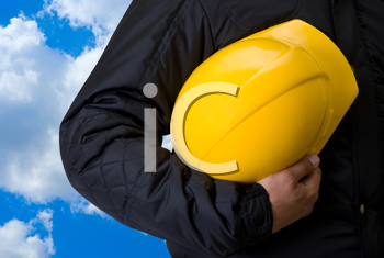 Royalty Free Photo of a Yellow Helmet at Builder Hands Against a Blue Sky