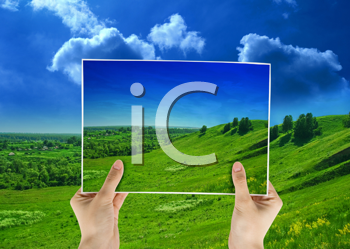 Royalty Free Photo of Hands Holding a Photo of a Hilly Landscape