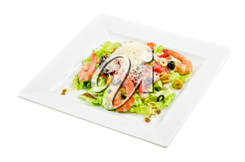 Salad with shrimps, eggs, caviar, calamaries, lettuce, olive, tomato and mozzarella on a white