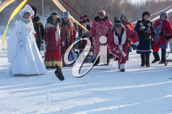 SVETLOE LAKE. ALTAISKIY KRAI. WESTERN SIBERIA. RUSSIA - DECEMBER 2, 2018: Folk national winter games (knock down the bottle from felt boots ) in the Altaiskaya Zimovka holiday - the first day of winter on December 2, 2018 in Altayskiy krai, Siberia, Russia.