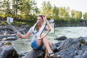 Woman taking selfie on mobile phone with stick on mountain river background