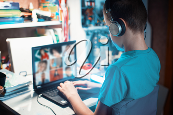 Distance learning or online education conference concept. Schoolboy studies at home and does school homework by laptop
