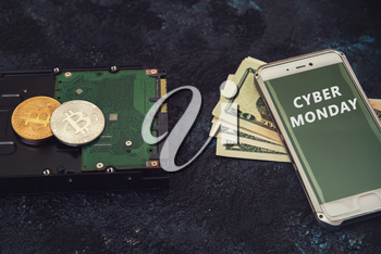 Bitcoin coins on the HDD and phone with Cyber Monday sign