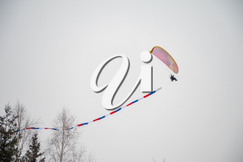 Paraglider is flying in the sky in the Altai winter mountains.