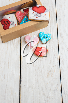 Gingerbreads for Valentines Day in gift box on white wooden background