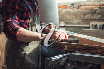Carpenter worker cutting wooden board with circular saw. Profession, carpentry and woodwork concept.
