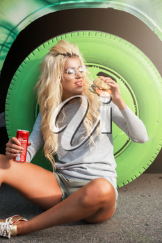 Rest in street, outdoor, people and leisure concept - beauty blonde young woman sitting on outdoor and eating