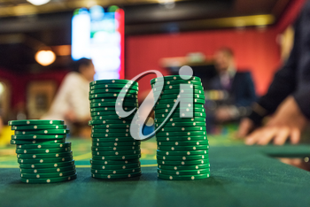 Casino, gambling and entertainment concept - stack of poker chips on a green table