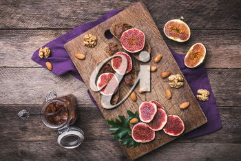 Sliced figs, nuts and bread with jam on choppingboard in rustic style. Autumn season food photo