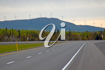 View of the Trans-Canadian Highway with electric wind mill towers in the background.