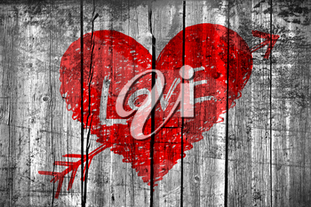 Drawing of abstract heart pierced by an arrow with word Love on grunge wooden wall background