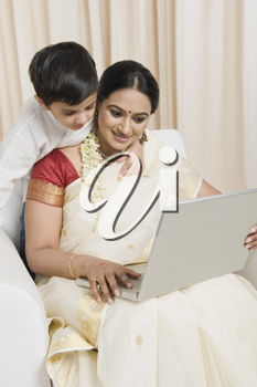 Woman using a laptop with her son standing behind her