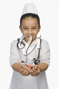 Girl dressed as a nurse and holding capsules and smiling