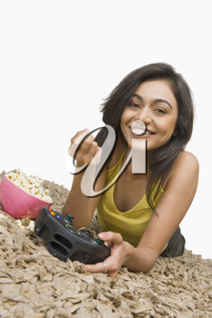 Portrait of a woman eating popcorn and playing video game