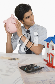 Real estate agent holding a piggy bank near his ear