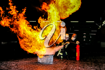 Firefighters training for fire fighting in Germany. Firefighter in fire protection suit spraying water to fire with smoke. Firefighter fighting fire attack, during training exercise