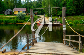 Ligatne ferry crossing on the bank of river Gauja. Ferry across river in Latvia. The ferry over Gauja river is the only crossing of this type in the Baltic States. Ferry is made of two boats fastened together on which there is a plank layer.