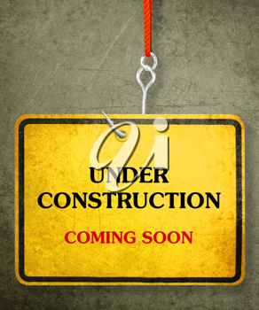 Alert yellow sign hanging by fishhook, conceptual image for under construction and coming soon