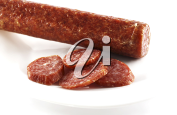 Smoked sausage cut by slices on a white dish