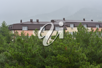 residential building with a wet roof after the rain against the backdrop of mountains in the fog