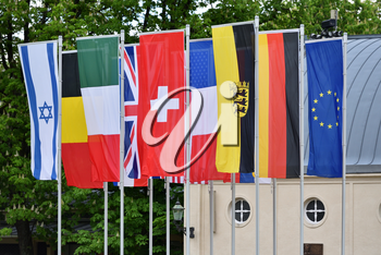 Flags of different countries in the park of the European city of Baden-Baden, Germany against the background of trees. Flags of the Commonwealth of Germany, Switzerland, France, America, England, Israel