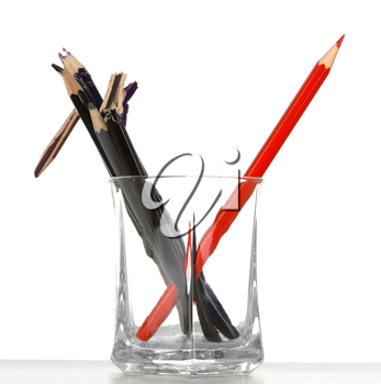 Royalty Free Photo of a Single Red Pencil Crayon With Other Pencil Crayons in a Glass