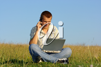 Royalty Free Photo of a Man Sitting on a Grass Holding a Laptop and Talking on a Cellphone