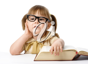 Royalty Free Photo of a Girl Wearing Big Glasses With an Open Book in Front of Her