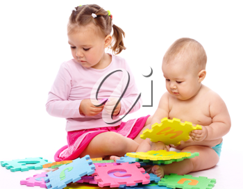 Royalty Free Photo of a Little Boy and Girl Playing With Foam Puzzle Pieces