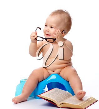 Royalty Free Photo of a Baby on a Potty With Reading Glasses and a Book