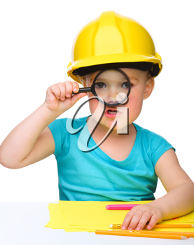 Royalty Free Photo of a Little Girl in a Hardhat Holding a Magnifying Glass