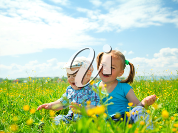 Royalty Free Photo of Two Children Sitting Among a Field of Flowers