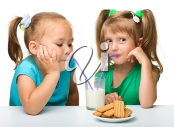 Royalty Free Photo of Two Little Girls Drinking Milk and Having Cookies