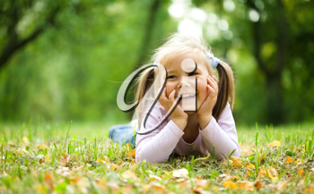 Royalty Free Photo of a Little Girl Lying on the Ground in a Park in Autumn